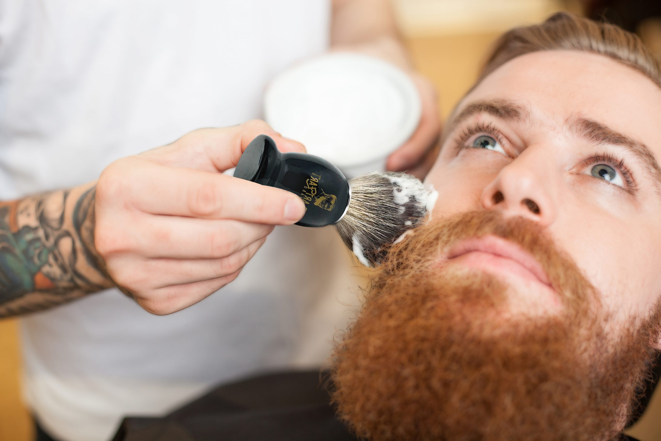 Close up of arms of professional barber preparing the beard of man for shaving. He is standing and applying shaving foam of human face. Young bearded man is looking up seriously